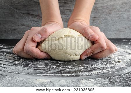 Woman Kneading Dough With Her Hands On Wooden Table On Dark Background. Homemade Baking