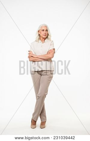 Full length portrait of beautiful adult woman 70s with gray hair smiling and looking on camera with arms folded isolated over white background