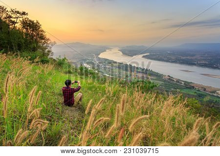 Travel Man Stand For Take Photo On Rock Stone Near Cliff At