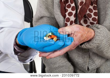 Close Up Doctor With Blue Gloves Giving Medical Pills To Elderly Woman