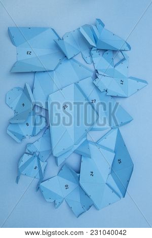 Details And Parts Of The Papercraft Scheme For Assembling Paper Or Cardboard Figures On A Blue Backg