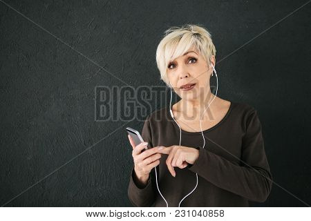 Positive Elderly Woman Listening To Music. On A Dark Background. The Older Generation And New Techno