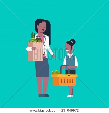 African American Woman With Daughter Holding Paper Bag And Shopping Basket Full Of Grocery Products