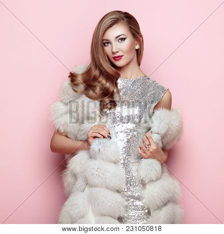 Fashion Portrait Young Woman In White Fur Coat. Girl With Elegant Hairstyle Posing On A Pink Backgro