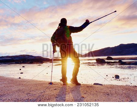 Happy Disabled Man On Beach Holding His Forearm Crutches Above Head, Warm  Sunset In Background
