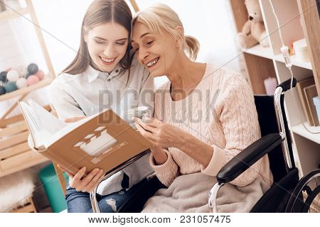 Girl Is Caring For Elderly Woman In Wheelchair At Home. They Are Looking At Photos In Photo Album.