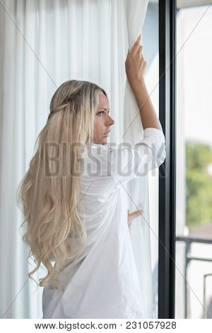 Blonde Slim Woman Long Hair Opens White Curtains