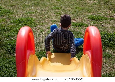 Child Plays At Playground With Green Grass.