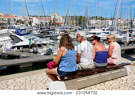 Lagos, Portugal - June 9, 2017 - Four Tourists Sitting On A Bench Looked At The View Of Boats And Ya