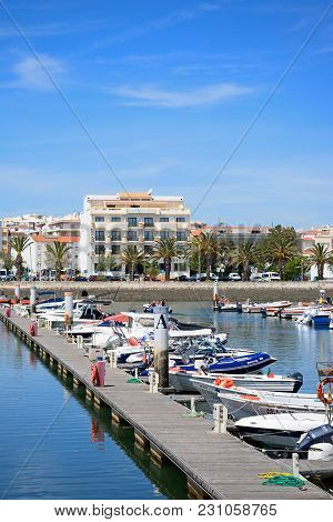 Lagos, Portugal - June 9, 2017 - Boats Moored Against A Pontoon With Town Buildings To The Rear In T