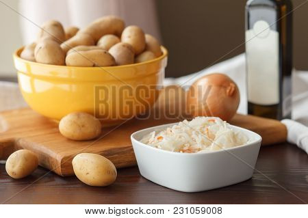 Ceramic Yellow Bowl With New Potatoes, Onion, Sauerkraut And Olive Oil Wooden Table. Ingredients For
