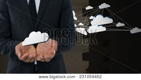 Digital composite of Cloud icons and Businessman with hands palm open and dark background