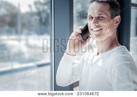 Unfinished Conversation. Pleasant Joyful Confident Man Standing Near The Window Having Phone Convers