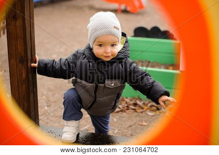 Cute Little Boy Dressed In Warm Clothes And Hat Walking On The Playground On The Cloudy Autumn Day