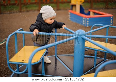 Cute Little Boy Dressed In A Warm Hat And Jacket Riding On The Carousel On The Playground