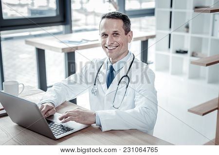 Ready To Work. Satisfied Confident Handsome Doctor Sitting On His Workplace Smiling And Using The La
