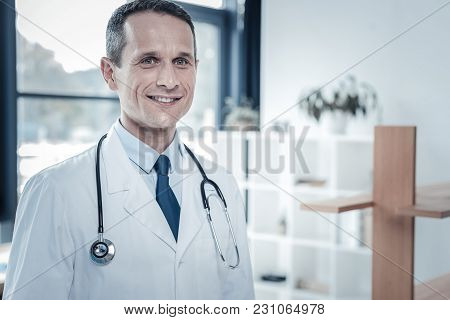 Best Professional. Responsible Pleasant Qualified Medic Standing In The Bright Room Looking Straight