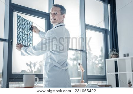 Simply Work Day. Satisfied Pleasant Qualified Doctor Standing In His Cabinet Holding X-ray Scan And