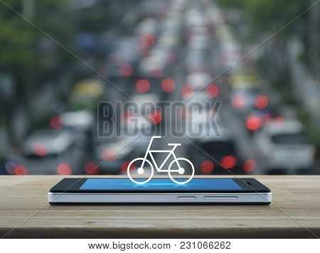 Bicycle Flat Icon On Modern Smart Phone Screen On Wooden Table Over Blur Of Rush Hour With Cars And