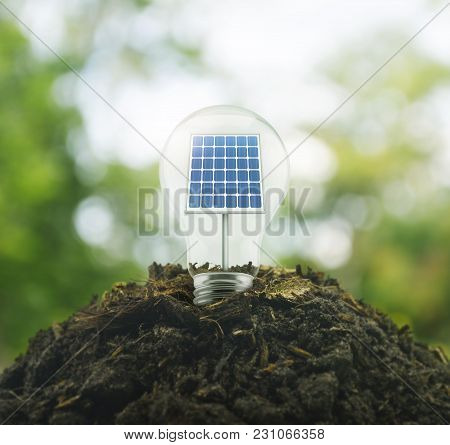 Light Bulb With Solar Cell Inside On Pile Of Soil Over Green Environment, Ecological Concept