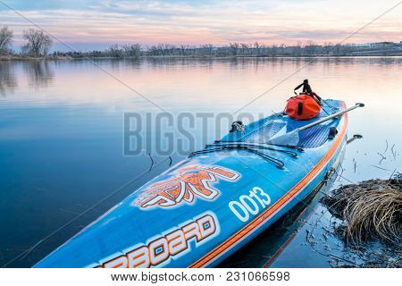 Fort Collins, CO, USA - March 11, 2018: Stand up paddleboard by Starboard with a waterproof duffle and a paddle on a calm lake after sunset.