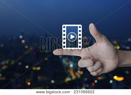 Play Button With Movie Icon On Finger Over Blur Colorful Night Light City Tower, Cinema Online Conce