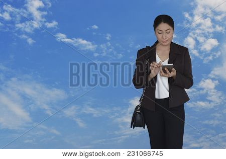 Asian Businesswoman In Black Suit Pointing Finger To Modern Smart Phone Screen Over Blue Sky With Wh