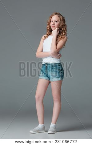 Full Length Of Young Slim Female Girl In Denim Shorts On Gray Studio Background. Studio Portrait Of