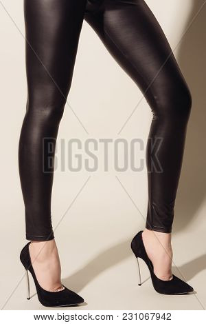 Women's Legs In Black Tight-fitting Leather Trousers And High-heeled Shoes Standing