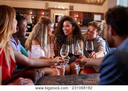 Six young adults making a toast with wine at a bar