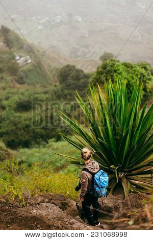 Woman With Camera And Backpack Near One Huge Agave Plant With Arid Landscape Of Location Called Cord