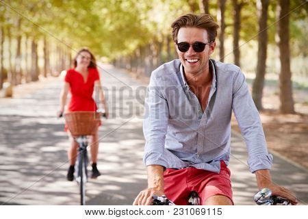 Young white adult couple riding bikes on a quiet sunny road