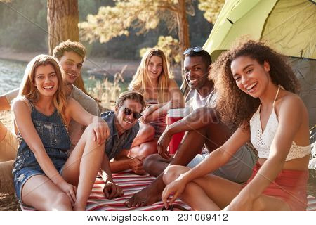 Friends relaxing on a blanket by a lake, close up
