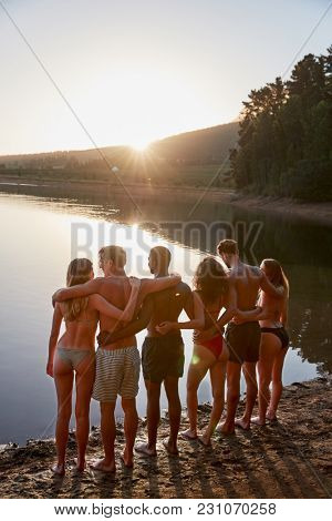 Young adult friends standing on lakeshore, vertical