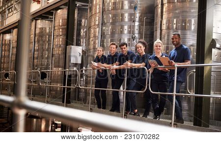 Staff at a wine factory smiling to camera from a gangway