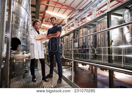 Male and female wine factory technicians looking to camera