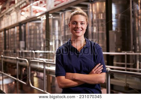 Portrait of a young white woman working at a wine factory