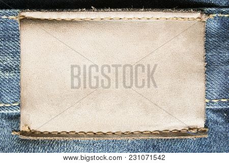 Blank Yellow Leather Clothes Label On Blue Denim Background Closeup