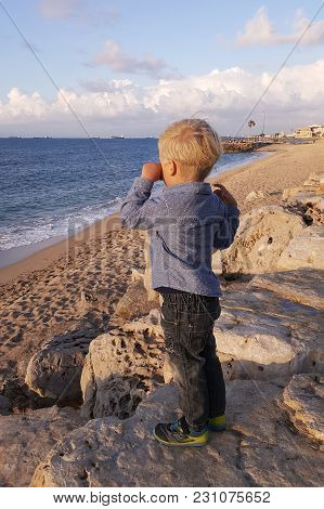 Little Boy Standing On Beach Wiping His Tears, Waiting And Looking At Ships. Haifa