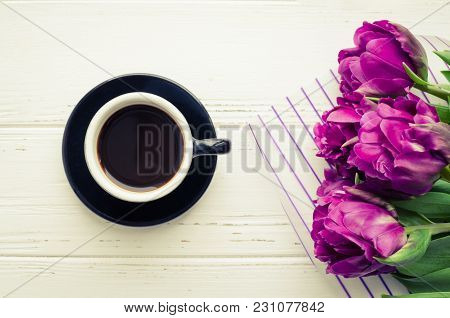 Coffee And Flowers Tulip. Cup Of Coffee And Purple Tulips On White Wooden Table. Breakfast On Mother