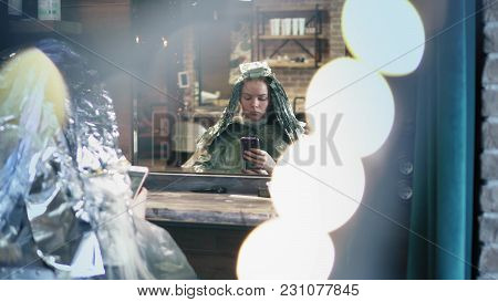 Beautiful Hipster Woman With Head Fully Covered With Hair Dye Is Sitting In Chair In Hair Salon And