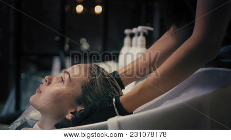 Hairdresser Softly Wraps Woman's Long Blonde Hair In A Towel In Sink After Washing. Profile Angle.