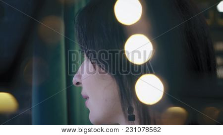 Beautiful Brunette Is Looking Out The Window, With Green Background. Closeup, Profile. Portrait. Twi