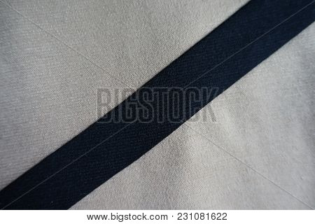 Black Ribbon Sewn To Beige Fabric Diagonally