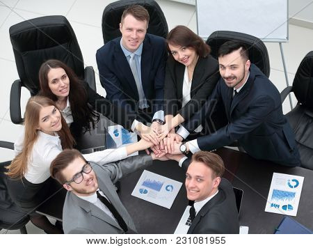 business team with hands clasped together on Desk