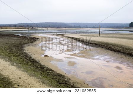 The Landscape Is Lowered Reservoir Contains Water And Markers In The Form Of Poles Of Wood. Directio