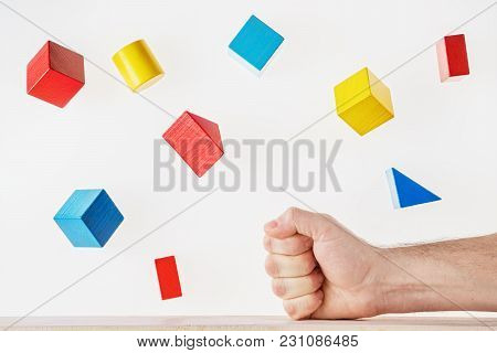 The Fist Strikes The Table And The Multicolored Wooden Geometric Shapes Fly Around. Concept Of Creat