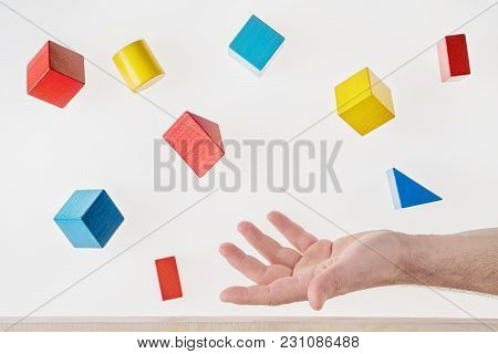 Male Hand Juggling Colorful Wooden Shapes. Concept Of Creative, Logical Thinking. Floating Shapes.