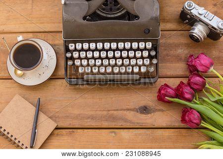 Dark Gray Retro Typewriter With White Keys An White Ranunculus Flowers Over Wooden Background. Copy