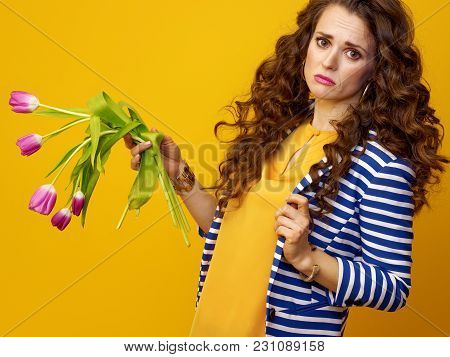 Sad Modern Woman On Yellow Background Holding Wilted Flowers